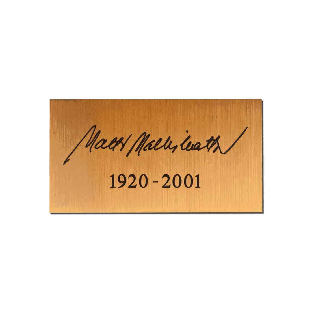 Pronssilaatta nimikirjoituksella hautakiveen.
