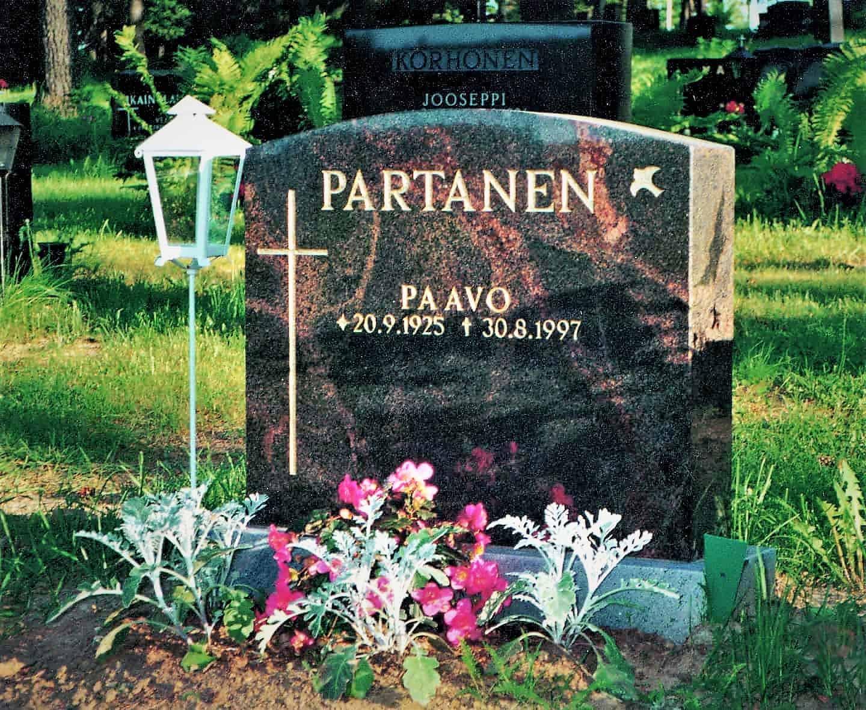 Hautakivi Partanen on musta ja siinä on punaisia alueita. Hautakiven Vasemmassa reunassa on risti ja oikeasa reunassa on lintu.