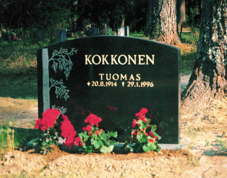 Kuvassa on hautakivi Kokkonen on yläosasta kaareva ja sen vasemmassa reunassa on puu.