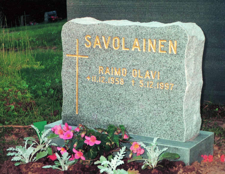 Kuvass on hautakivi Savolainen, joka on vaaleanharmaa väritykseltään ja muodoltaan suorakulmainen, mutta reunoissa on laineita. Teksti hautakivessä ja sen vasemmalla puolella oleva risti tulevat molemmat kullan värisinä.