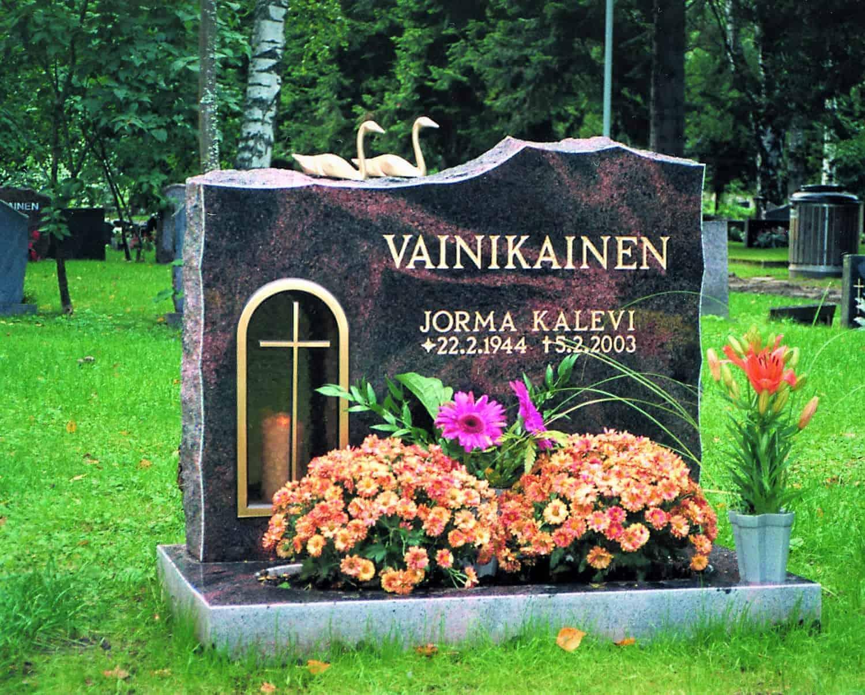 Hautakivi Vainikainen on musta hautakivi, jossa menee punertavia kuviointeja. Hautakiven vasemmassa reunassa on kullattu syvennys kynttilälle ja sen lasisessa ovessa on risti.