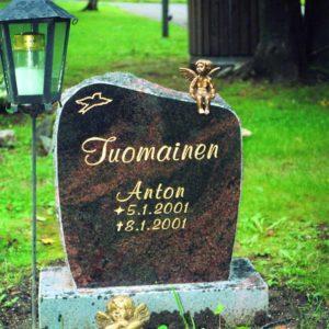 Hautakivi Tuomainen on pienehkö mustan värinen hautakiv, jonka läpi menee punertavia kuviointeja. Hautakiven vasemmassa reunassa in ylhäällä pronssinen lintu.