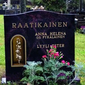 Hautakivi Raatikainen on mustan värinen hautakivi, jossa on halkeileva liila kuviointi. Myöskin hautakiven vasemmassa reunassa on kullattu syvennys, jossa on kukka pronsikoriste.