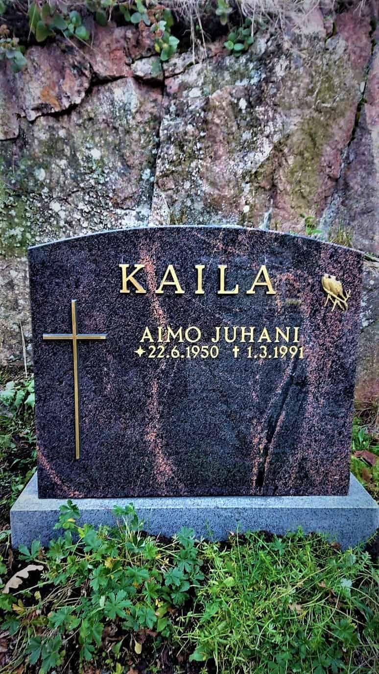 Kuvassa on hautakivi Kaila, joka on väritykseltään musta, mutta siinä menee halkeaman näköisiä kuviointeja punertavalla sävyllä. Myöskin hautakiven vasemmassa reunassa on risti.