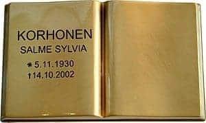 Kuvassa on Pronssikirja (muistolaatta kirja). Kirja on kullattu ja avonainen. Kirjan vasemmalla sivulla on teksti mustalla.