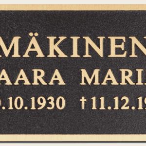 Pronssinen muistolaatta hautakiveen, tummalla pohjalla, kirkas teksti.