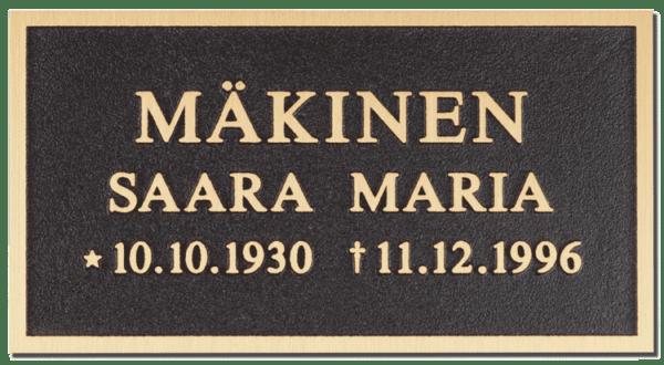 Muistolaatta kohokaiverruslaatta kohoreunuksella on hautakiveen tuleva muistolaatta. Muistolaatan kehystys ja teksti tulee pronssilla ja pohja mustalla.