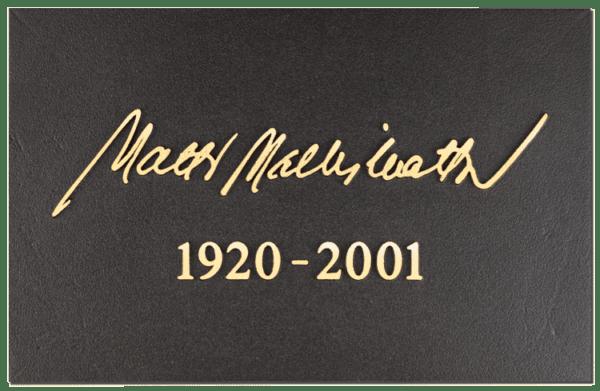Tässä kuvassa on muistolaatta kohokaiverruslaatta nimikirjoituksella, joka on suorakulmion mallinen. Muistolaatan väritys on musta muutoin, piatsi teksti on pronssinen.