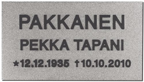 Tässä kuvassa on muistolaatta kromattu kohokaiverruslaatta, joka on neliskanttinen. Sen teksti on mustalla ja muutoin väritys on harmaa.
