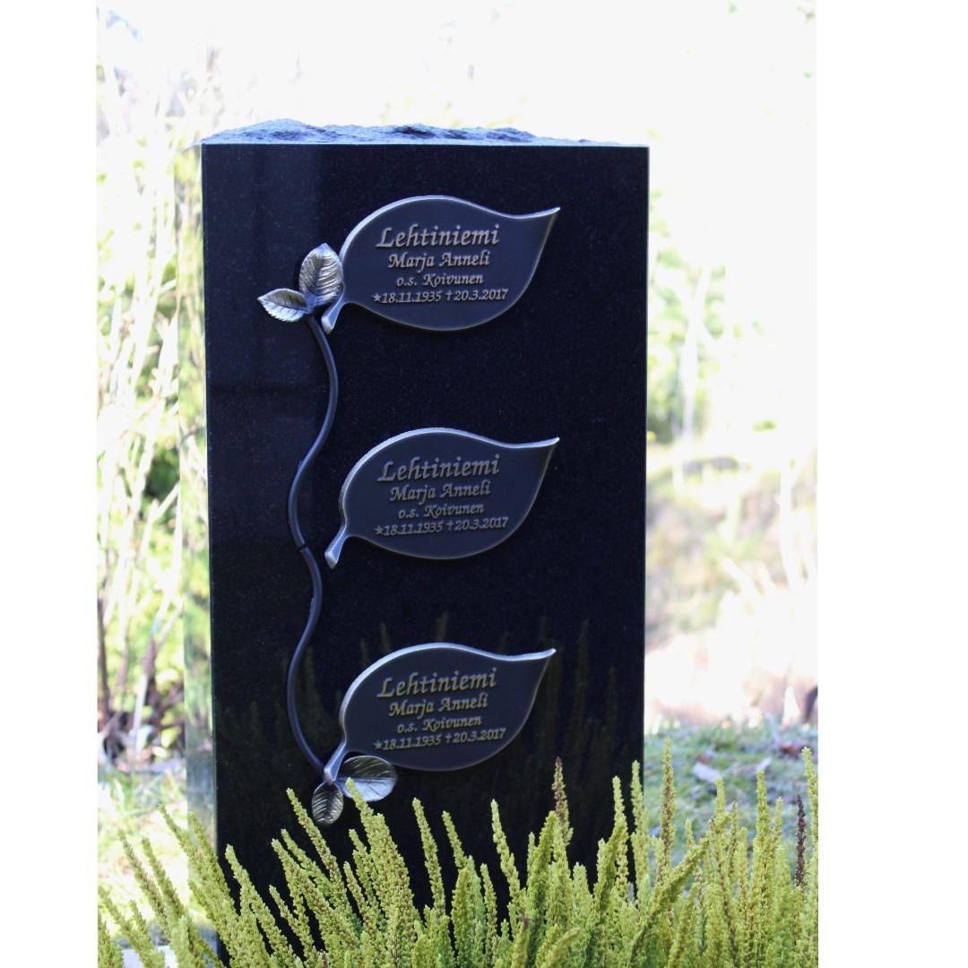 Hautakivi Lehdet on musta hautakivi, jossa on kolme suurta lehteä päällekkäin.
