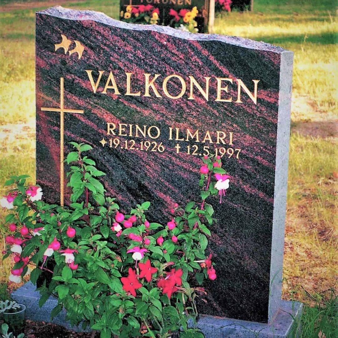 Kuvassa on hautakivi Valkonen, joka on värityseltään musta ja siinä kulkee punertavia raitoja. hautakiven vasemmassa reunassa on risti ja sen yläpuolella kaksi pientä lintua.