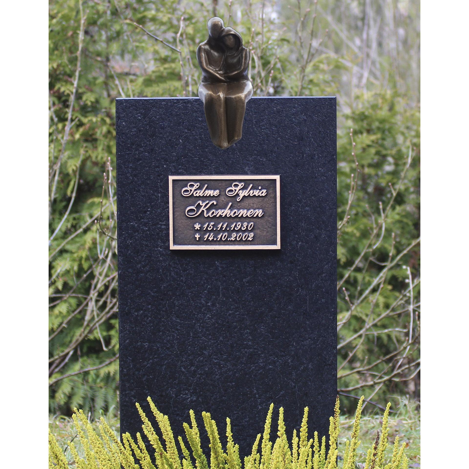 Kuvassa on musta hautakivi Pariskunta. Pronssinen pariskunta istuu hautakiven päällä ja muistolaatta tulee hautakiven yläosaan.
