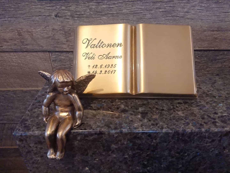 Kuvassa on hautakivi koristeet muistolaatta kirja kirkas pronssikirja ja enkeli. Kirja ja enkeli ovat pronssisia ja kirjan teksti on musta.