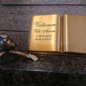 Muistolaatta kirja kirkas pronssikirja ja lintu oksalla on hautakivi koriste. Kirja on kullan värinen ja lintu oksalla musta. Kirjan teksi on musta.