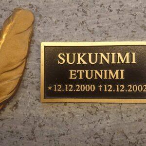 Muistolaattapaketti hautakiveen.