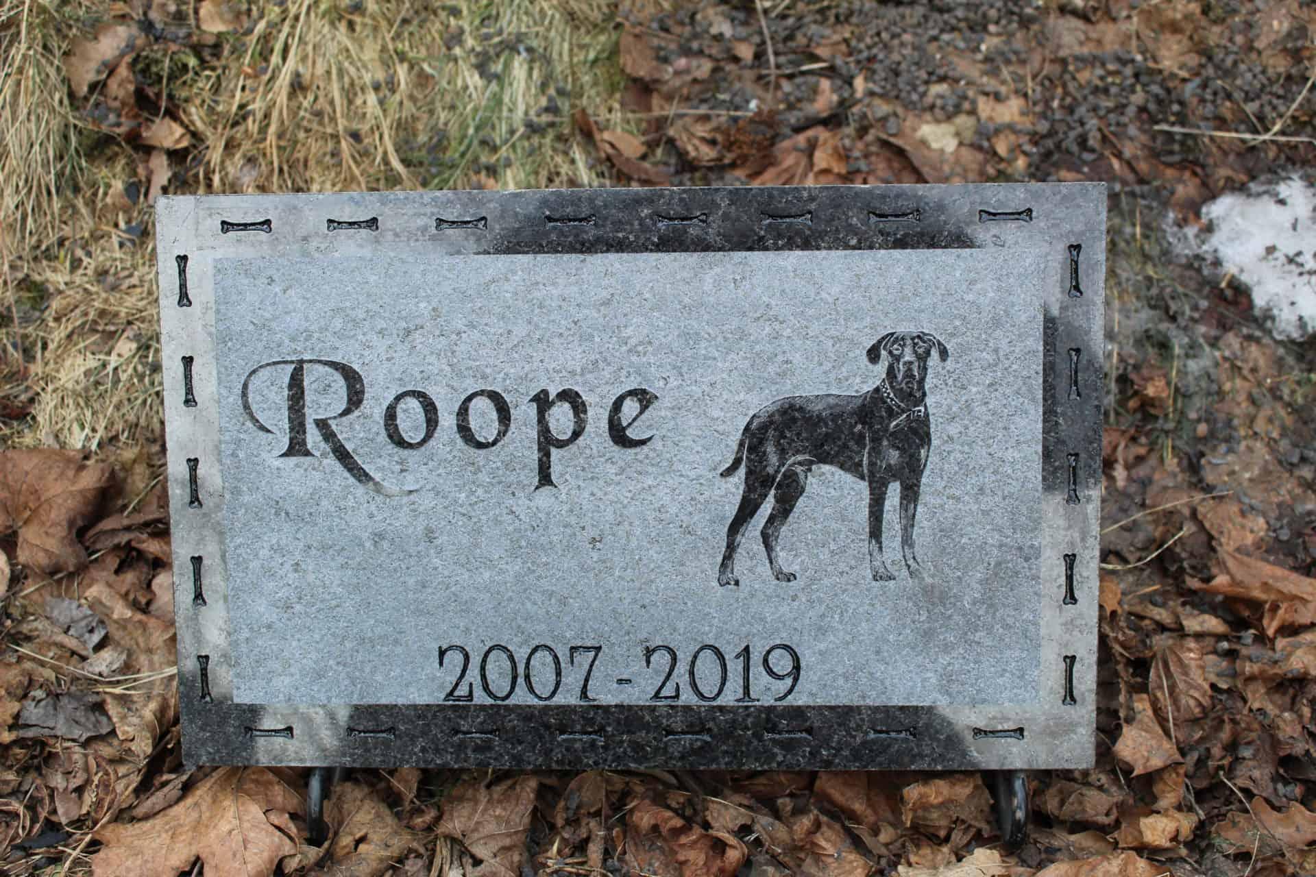 Kuvassa on Koiran hautakivi tai ennemminkin muistokivi koiralle. Muistolaatassa on teksti vasemmalla ja oikealla on koiran kuva. Koiran hautakivestä saa tehtyö kuvaa vaihtamalla kissan tai vaikka hevoden hautakiven.